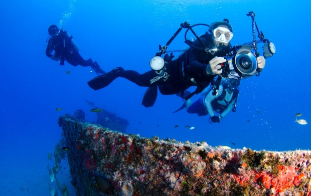 Divers with camera equipment on a shipwreck