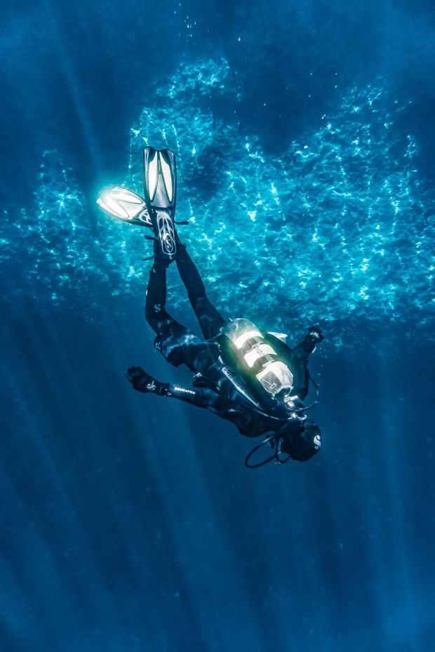 Diver submerging through shafts of light